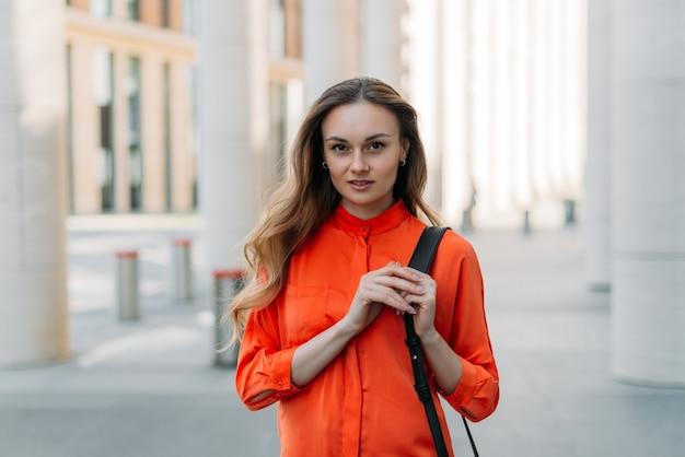 Hermosa chica caucásica con cabello suelto en la ciudad mira a la cámara