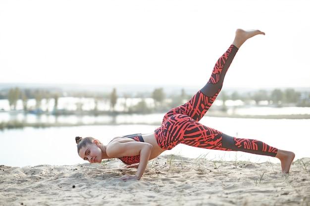 Hermosa chica caucásica en ropa deportiva brillante y polainas hace la barra en la naturaleza.