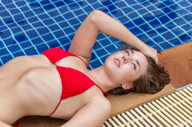 Hermosa chica caucásica sexy sonriente y sexy en bikini cerca de la piscina.