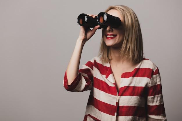Hermosa chica en chaqueta tiene binoculares