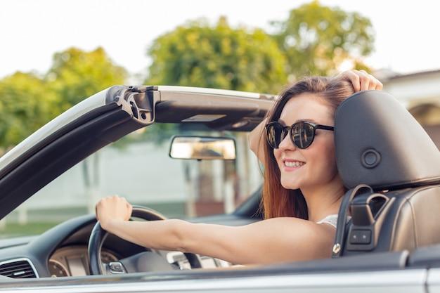 Hermosa chica en el coche descapotable cabrio en un día soleado en una ciudad