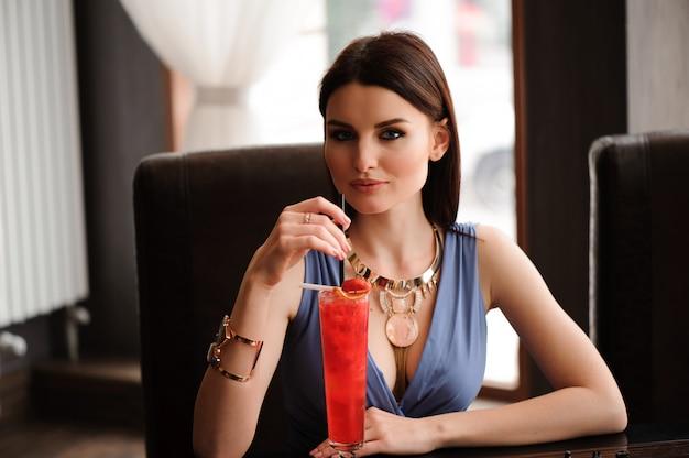 Hermosa chica con un cóctel en el café.