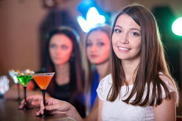 Hermosa chica con un cóctel en sus manos sonriendo.