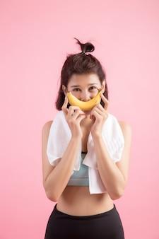 Hermosa chica comiendo bananas después de hacer ejercicio para controlar el peso.