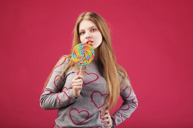 Hermosa chica comiendo piruleta rayada grande