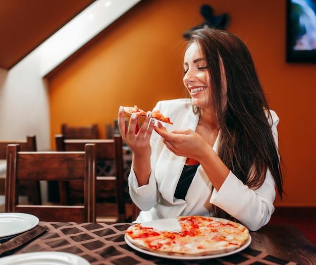Hermosa chica comiendo pizza en el restaurante