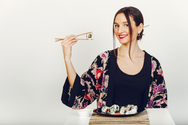 Hermosa chica comiendo un sushi en un estudio