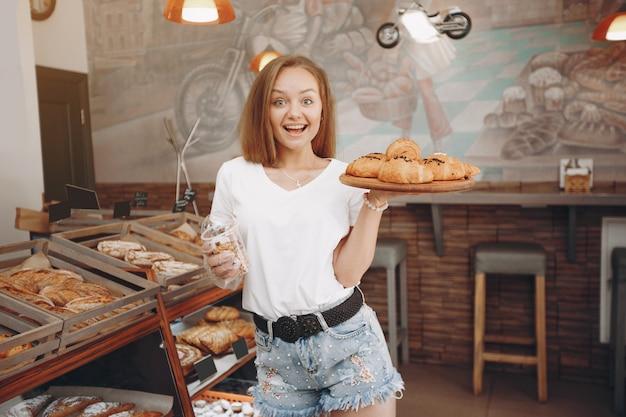 Hermosa chica compra bollos en la panadería