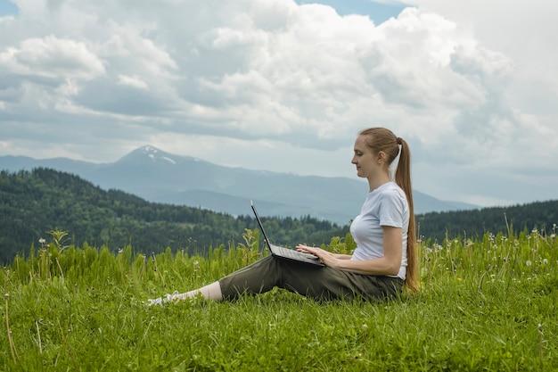 Hermosa chica con una computadora portátil sentado en la hierba verde