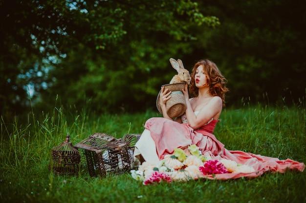 Hermosa chica con un conejo al aire libre en día de verano