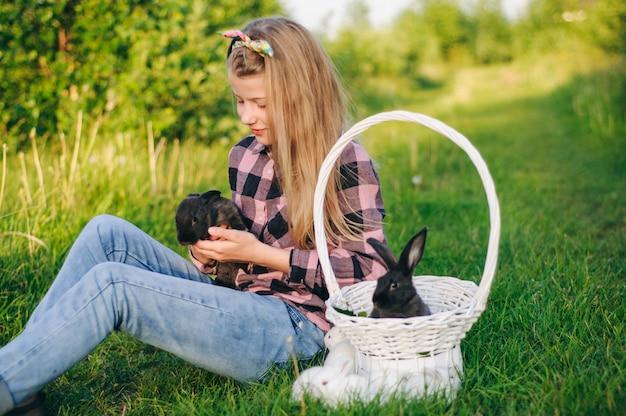 Hermosa chica con un conejo. niña ríe y besa a un conejo. camisa de camisa y jeans. conejo de pascua. reír en voz alta