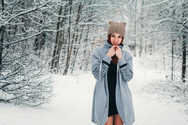 Hermosa chica se congela en el invierno en el bosque. foto en tonos fríos