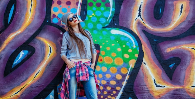 Hermosa chica cool en sombrero y gafas de sol sobre la pared de graffiti