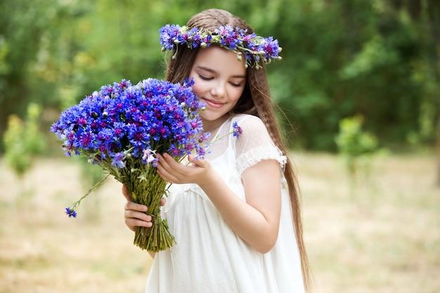 Hermosa chica en una corona de flores de aciano y con un ramo de flores en la cesta.
