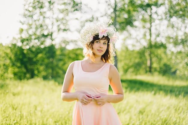 Hermosa chica con una corona de flores en la cabeza sonriendo al aire libre en un día soleado