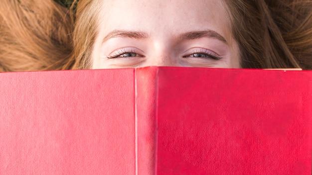 Hermosa chica cubriendo su boca con un libro rojo