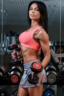 Hermosa chica con cuerpo sexy en el gimnasio