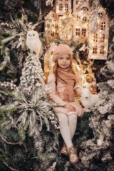 Hermosa chica en una decoración navideña con muchos árboles bajo la nieve y las luces