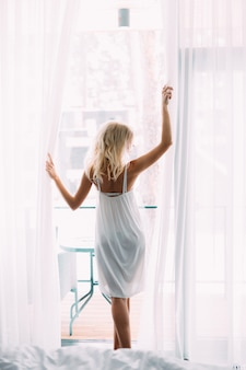 Hermosa chica delgada con el pelo largo weared en vestido blanco de pie descalzo cerca de la ventana grande. vista trasera