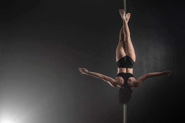 Hermosa chica delgada con pilón, bailarina de barra femenina bailando sobre un fondo negro
