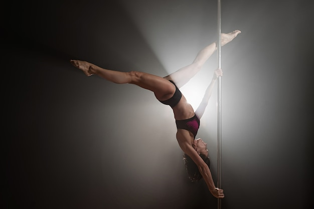 Hermosa chica delgada con pilón. bailarina de barra femenina bailando