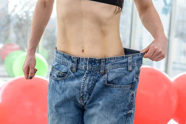 Hermosa chica delgada que muestra el resultado de la dieta después de hacer ejercicio físico