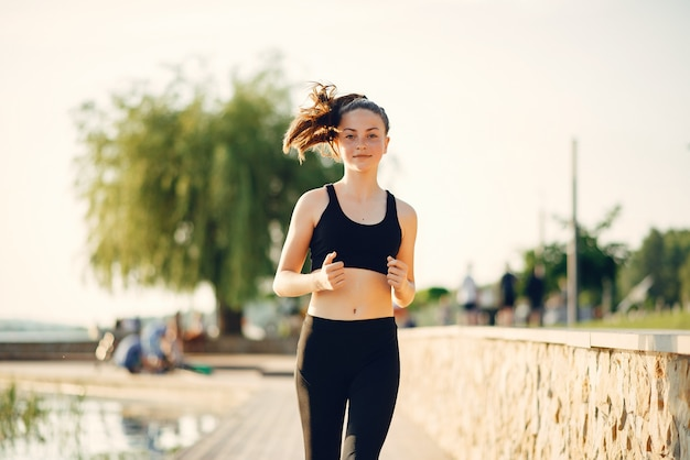 Hermosa chica deportiva en un parque de verano