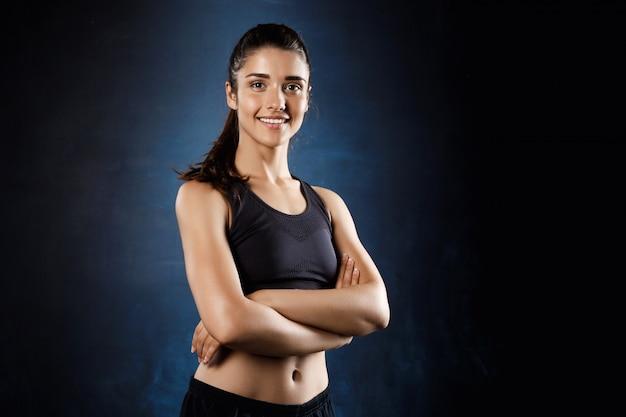 Hermosa chica deportiva posando con los brazos cruzados sobre la pared oscura.