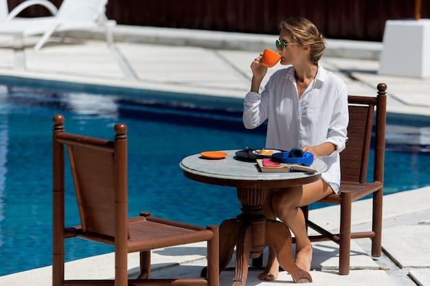 Hermosa chica desayunando cerca de la piscina