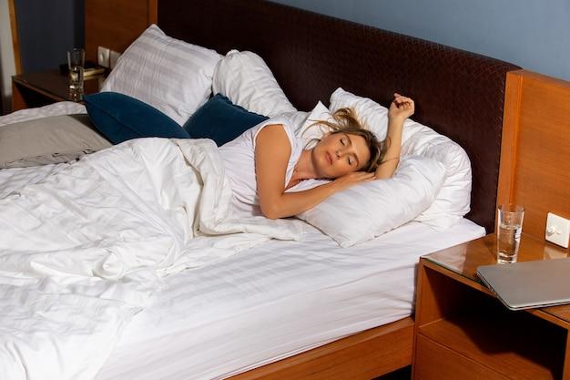 Hermosa chica se despierta en la cama.