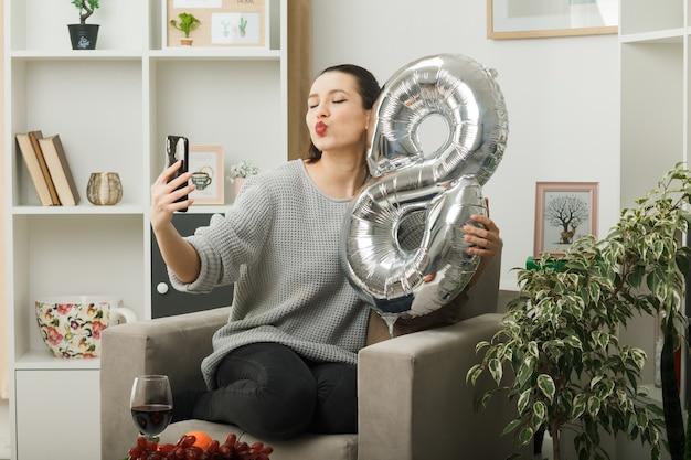 Hermosa chica en el día de la mujer feliz sosteniendo el globo número ocho sentado en un sillón en la sala de estar