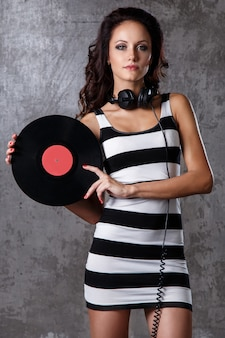 Hermosa chica con disco de vinilo.