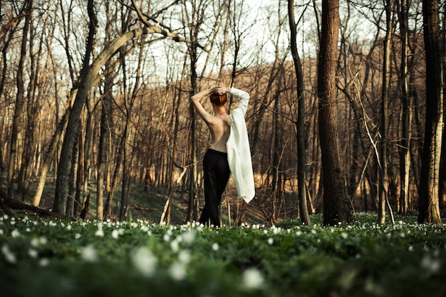 Una hermosa chica disfruta el bosque y la naturaleza
