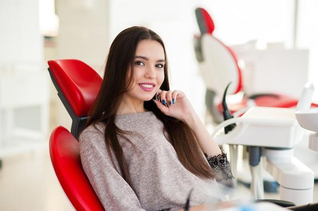 Hermosa chica disfruta de dientes sanos en odontología.
