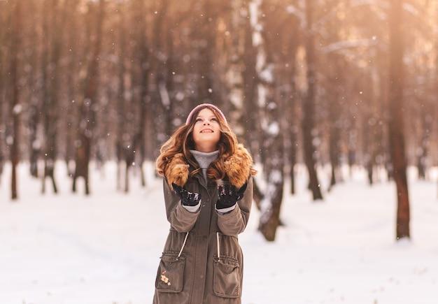Hermosa chica disfruta de la nieve en un parque de invierno en un día soleado