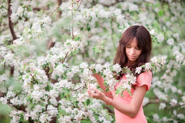 Hermosa chica disfrutando el olor en el jardín de cerezos de primavera