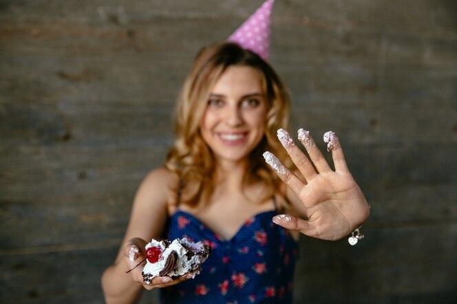 Hermosa chica divertida en sombrero festivo mostrando su palma en crema después de comer un pastel de cumpleaños
