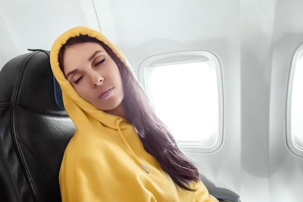 Hermosa chica duerme mientras vuela en el avión. concepto de viaje, vuelo.