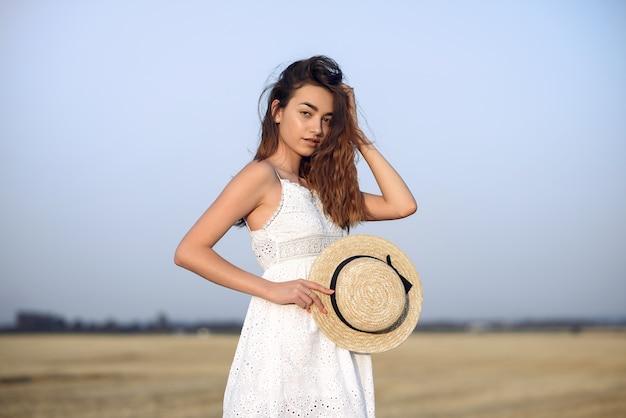 Hermosa chica elegante en un campo de trigo de otoño