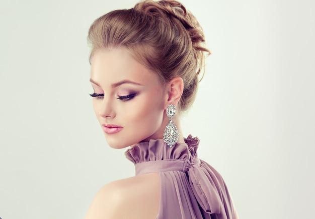 Hermosa chica con elegante peinado y grandes aretes de joyería