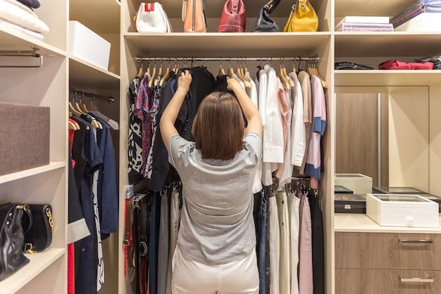 Hermosa chica está eligiendo ropa en su camerino