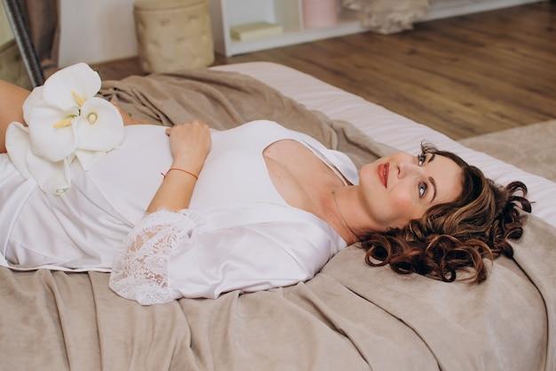 Hermosa chica embarazada vestida de blanco se encuentra en una cama con flores
