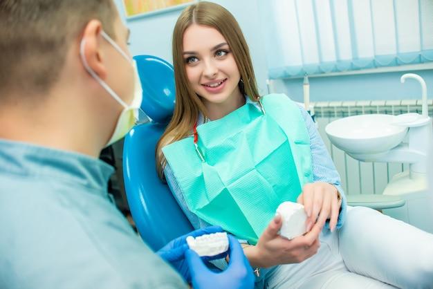 Hermosa chica emocional sentado en una silla dental junto a un médico masculino. clínica dental. doctor y paciente