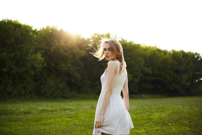 Hermosa chica en vestido en el parque mirando a la cámara