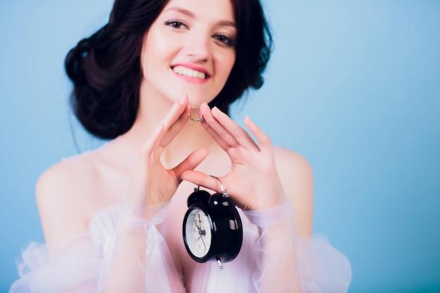 Hermosa chica encantadora en vestido de novia blanco, llegando tarde en la mañana y sosteniendo en su mano despertador retro y anillo