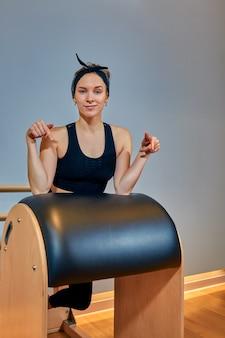 Hermosa chica - entrenador en top corto deportivo y leggings deportivos sonriendo está de pie en el simulador de estiramiento corporal