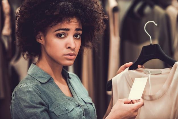 Hermosa chica es elegir ropa y mirando a cámara.