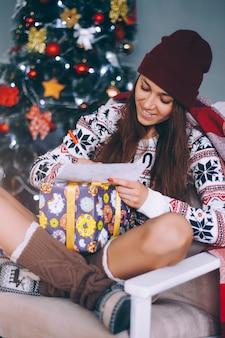 Hermosa chica escribe una carta al primer plano de santa claus sentado junto al árbol de navidad en casa.