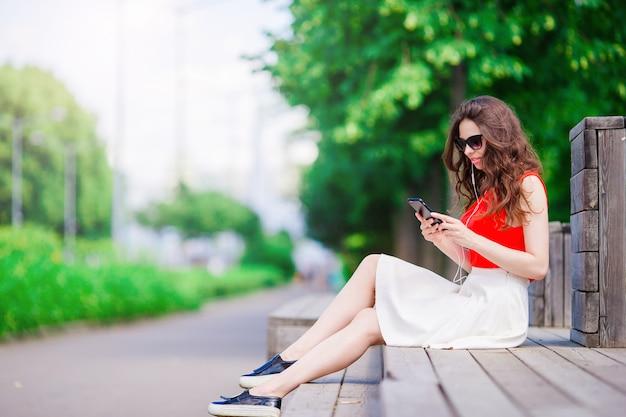 Hermosa chica escuchando música por teléfono inteligente en vacaciones de verano