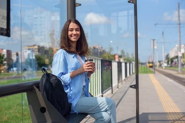 Hermosa chica espera el metro o el tranvía en la estación de transporte público en la mañana. mujer joven feliz con la taza de café en la estación pública.